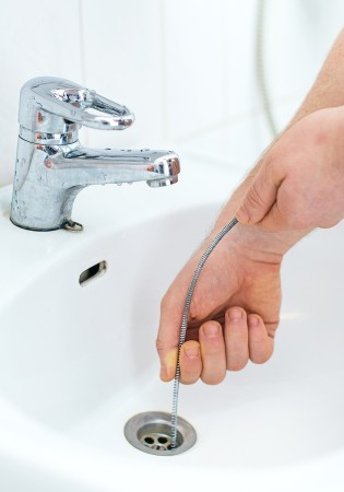 drain cleaning using a snake down a sink drain
