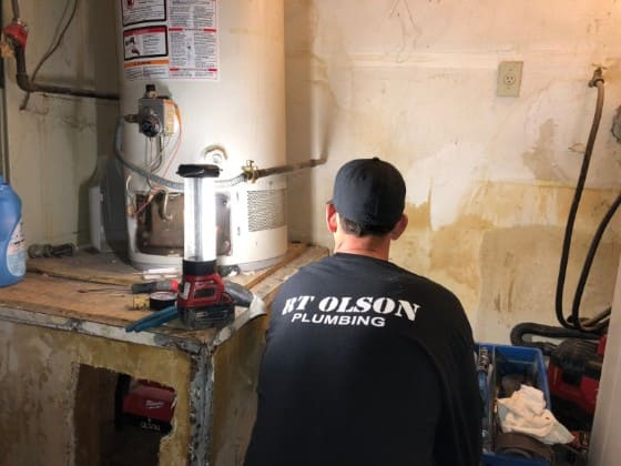 RT OIson plumber working on water heater repair