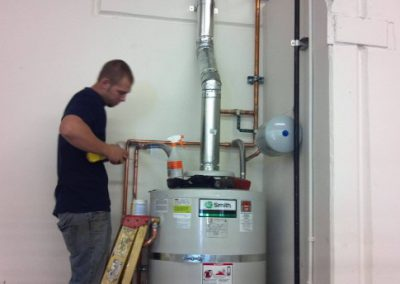 RT Olson plumber working on a water heater