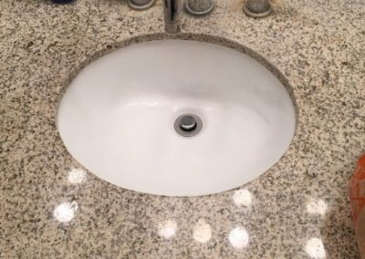 White sink installation in brown marble counter by RT Olson Plumbing