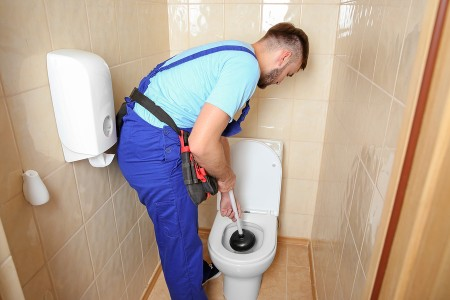 plumber using plunger to unclog a toilet