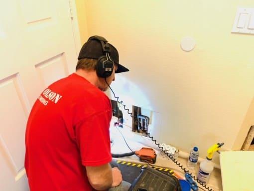 RT Olson plumber using leak detection equipment