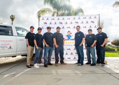 RT Olson plumbers in front of big banner and plumber's truck