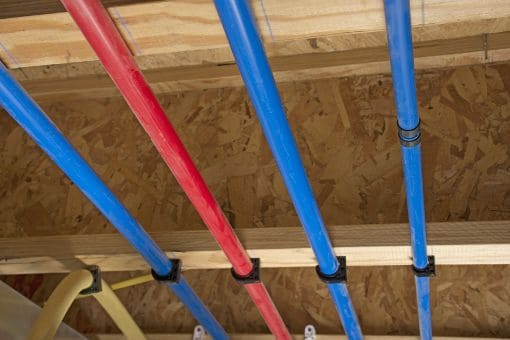 red and blue PEX pipe running in attic