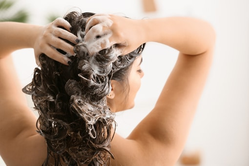 woman shampooing with softened water
