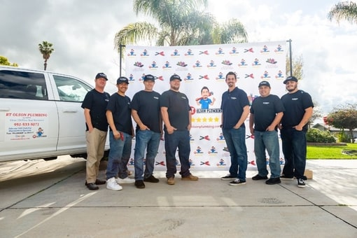 RT Olson plumbers in front of big banner