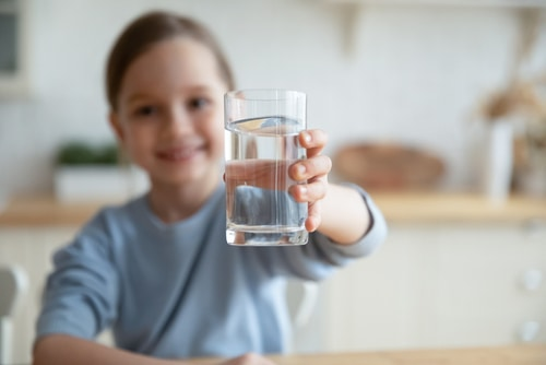girl holding glass of clean filtered water